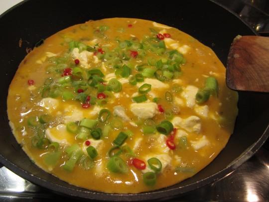 Phase 1: Eiermasse über die angebratenen Zwiebeln geben, Chili und Zwiebelgrün drauf, stocken lassen