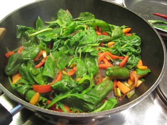 Spinat kommt zum Schluss auf das gebratene Gemüse, wo er in Ruhe zusammenfällt.