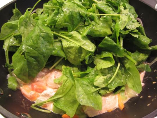 Spinat auf dem Curry drapieren